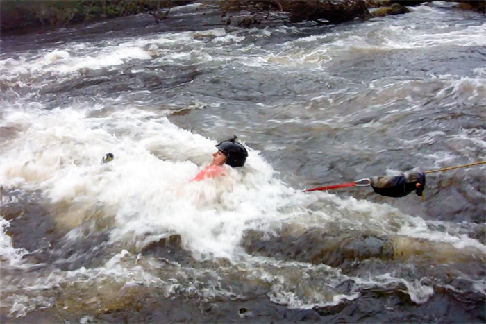 Person on rescue harness in white water