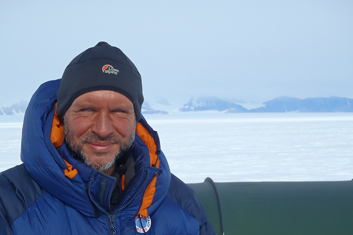 Lou Rudd, face tanned, wearing hat and duvet jacket against backdrop of polar landscape