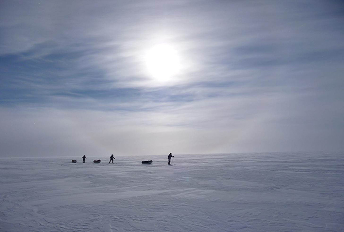 Three men hauling pulks in Antarctica, with milky sun through clouds