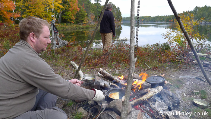 Man cooking pancakes on a campfire with some fall colours in the background