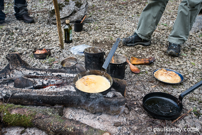Pan with pancake on a campfire