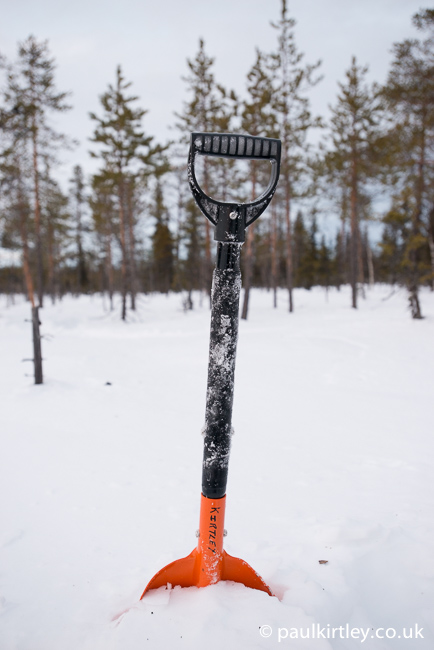 Snow shovel with snow on the shaft of the handle