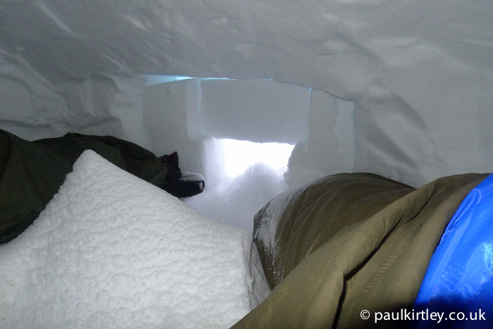 Inside a snow cave with a lot of snow blown in
