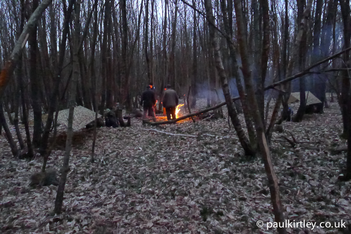 Men in woods standing around camp fire in winter