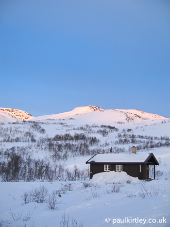 A small wooden hut agains the backrop of snow covered hills in Norway