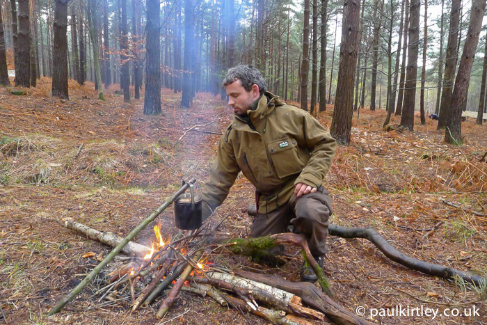 Ben Gray in front of campfire with cooking pot suspended on simple straight pot hanger