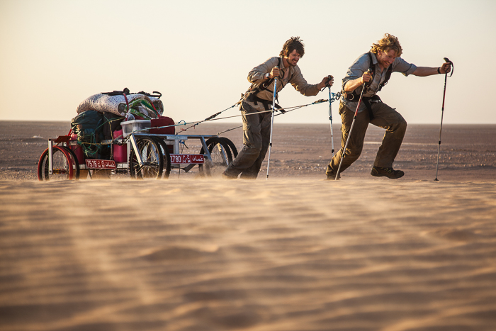 Two men pulling a cart across sand