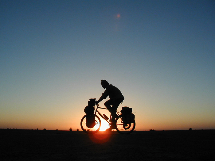 Al Humphries on a bike against a sunset