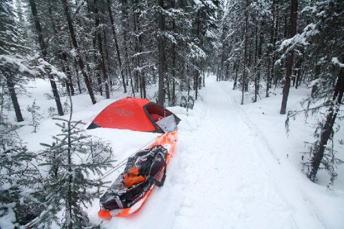 Red RAB tent and orange sled in white snow against black trees in the Yukon