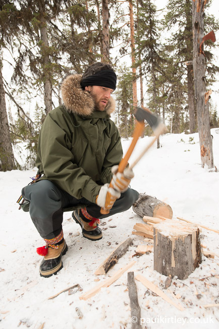 Forest man spitting wood in snow