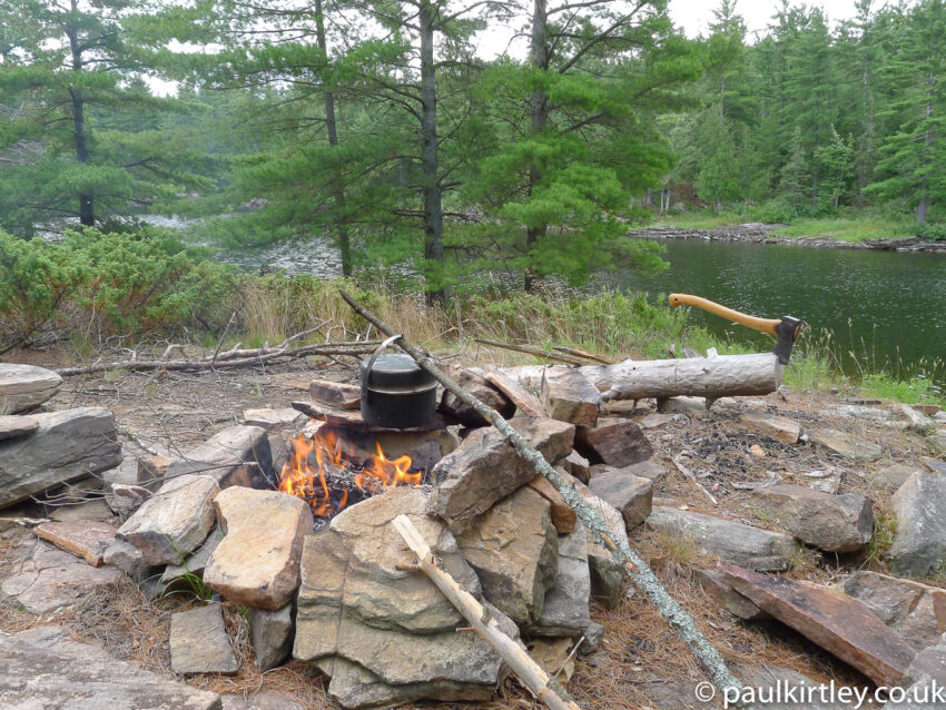 A rocky camping spot on the Canadian Shield, with an axe in a log