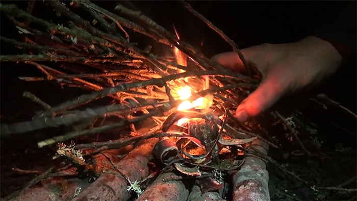 Hand holding sticks over burning birch bark