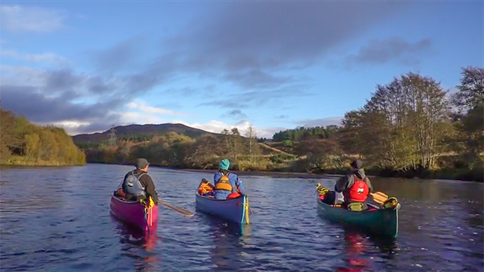Three canoeists with a blue shy background, illuminated by low autumn sunshine