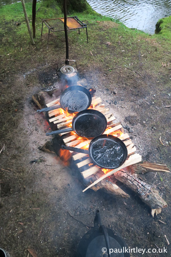 Split wood being used as a griddle in camp underneath frying pans - great campcraft