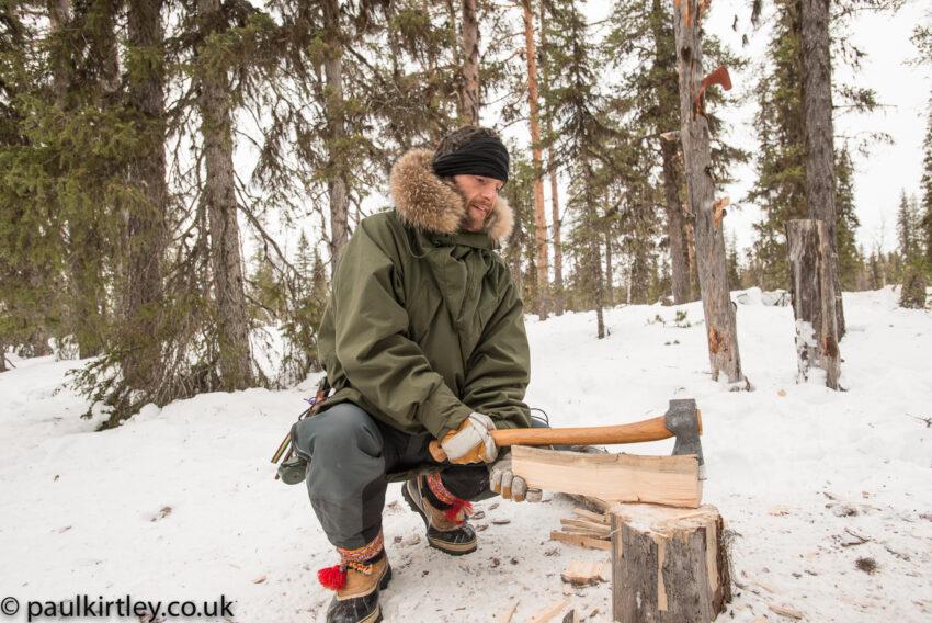 Man crouching on snow, while splitting firewood on treestump using axe