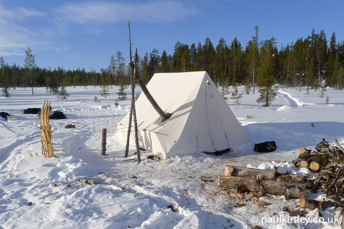 Snowtrekker tent in use in Sweden with wood processing area in front