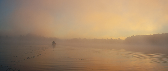 Man paddling a canoe on misty morning with orange light