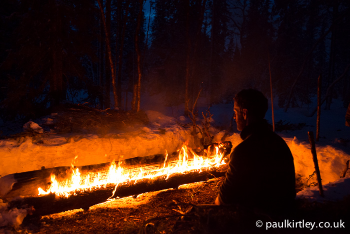 Man in front of big fire in woods