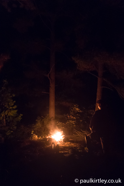 Camp illuminated by campfire with trees