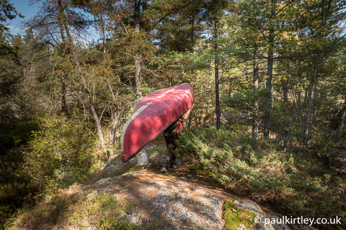 Red canoe being carried through the woods
