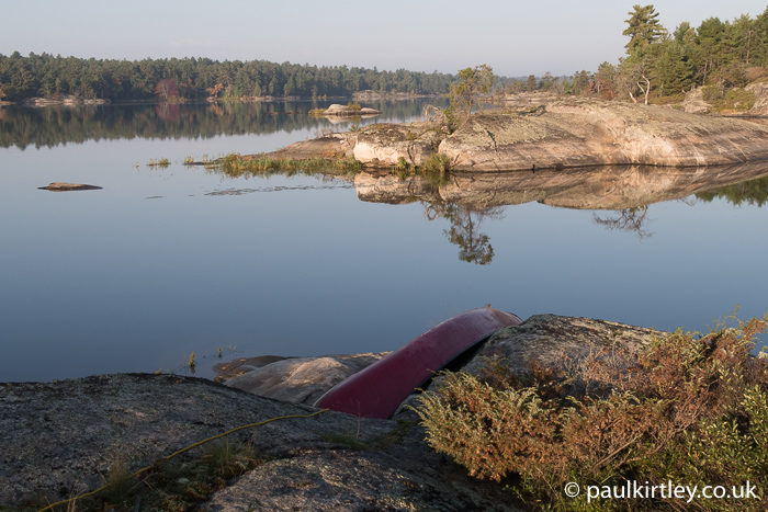 Canoe overturned on rocks with perfectly still water