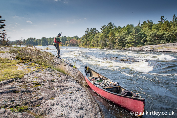 Man lining a canoe down edge of rough rapids