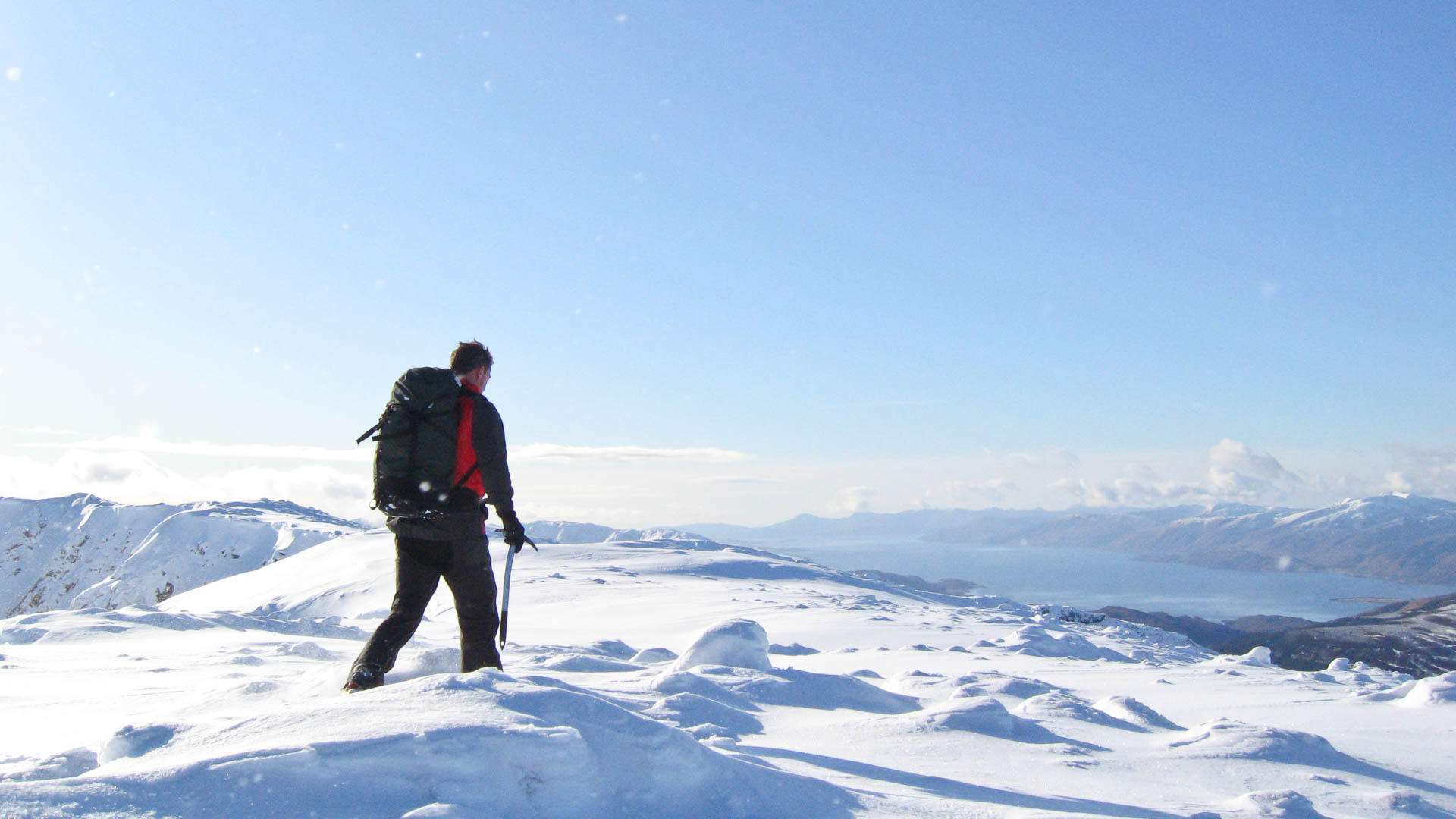 Man walking on broad snowy ridge west coast Scotland