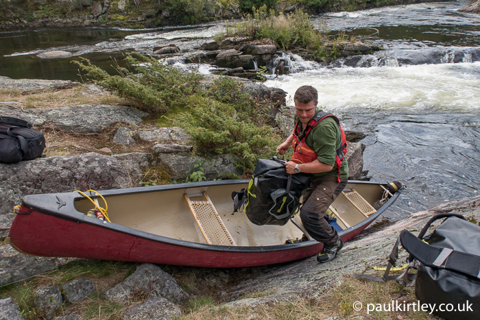 Paul Kirtley lugging bags out of a canoe