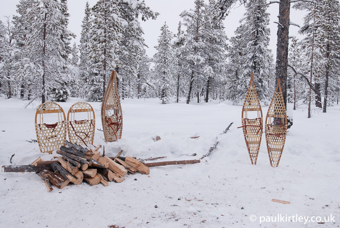 Snowshoes and firewood stacked on snow
