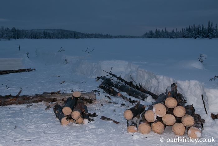 logs on snow in dusk