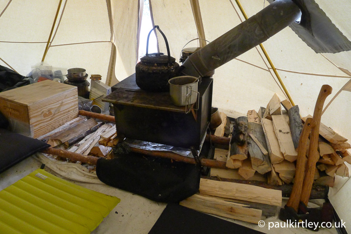 Inside of heated tent, including stove and stacked firewood