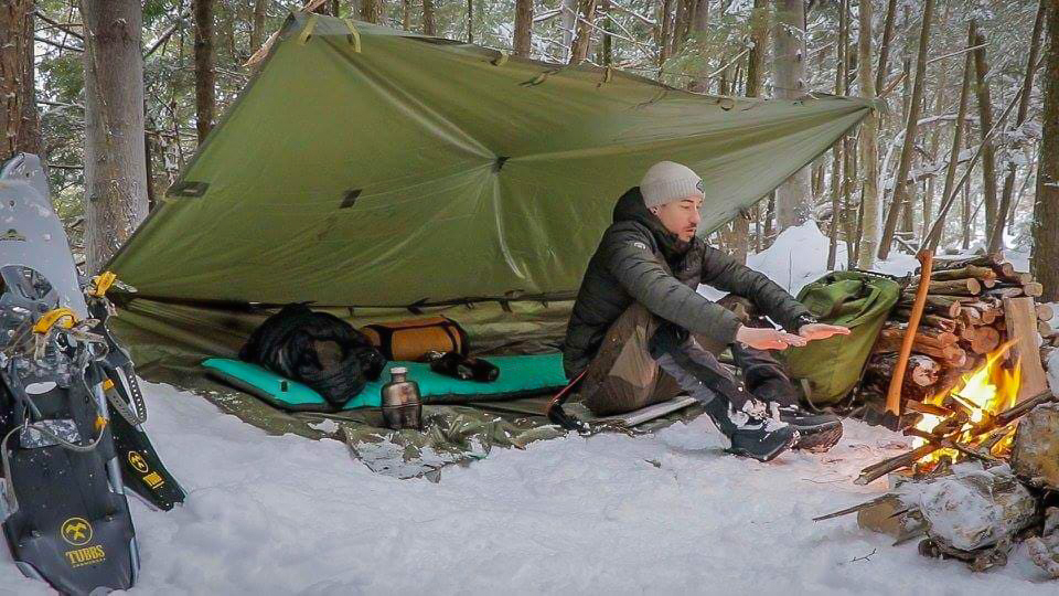 Man under tarp in snow with fire in front of him
