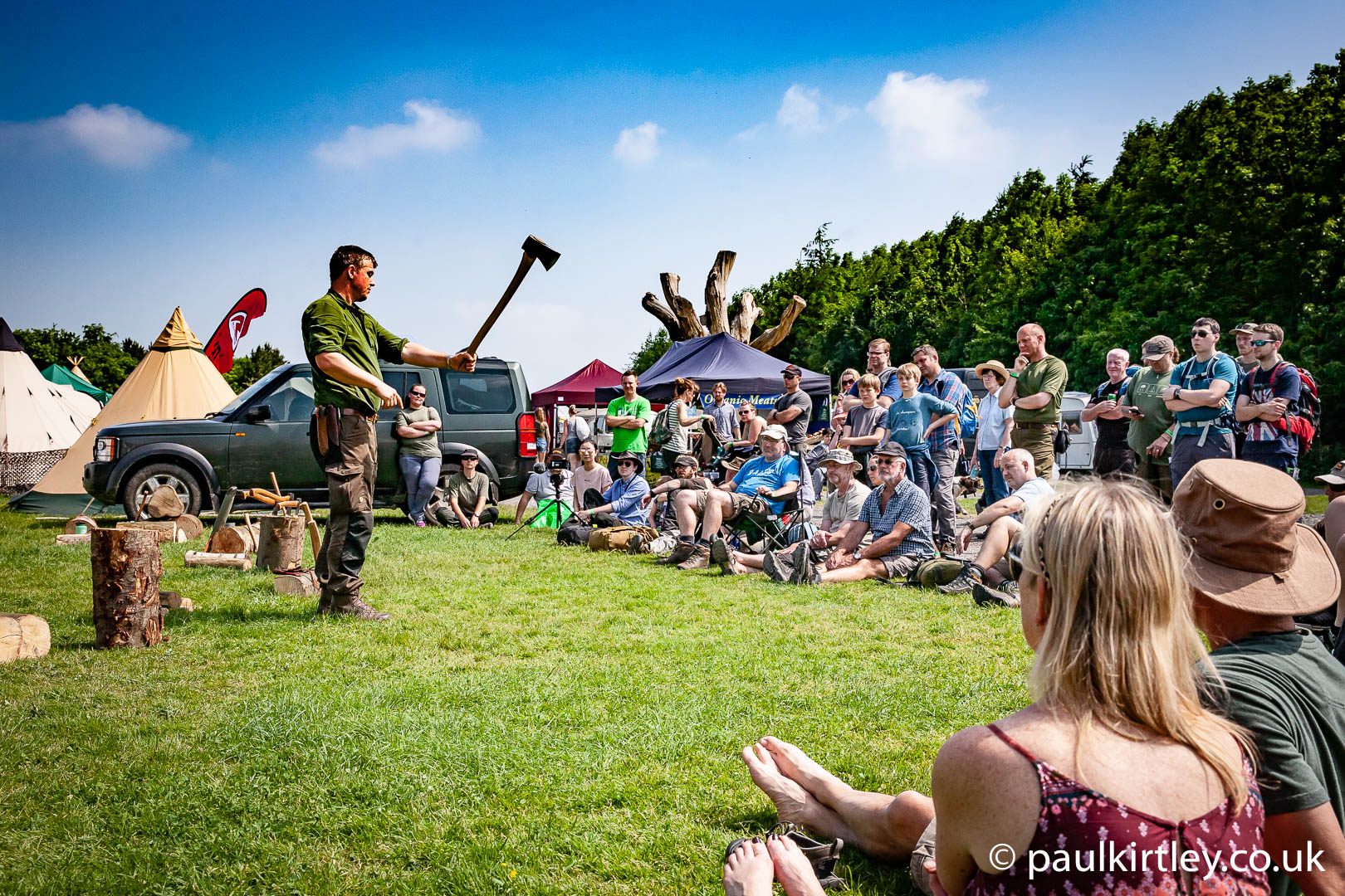 Paul Kirtley demonstrating axe skills to a gathering at the Bushcaft Show