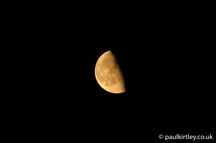 Quarter moon illuminated against black sky