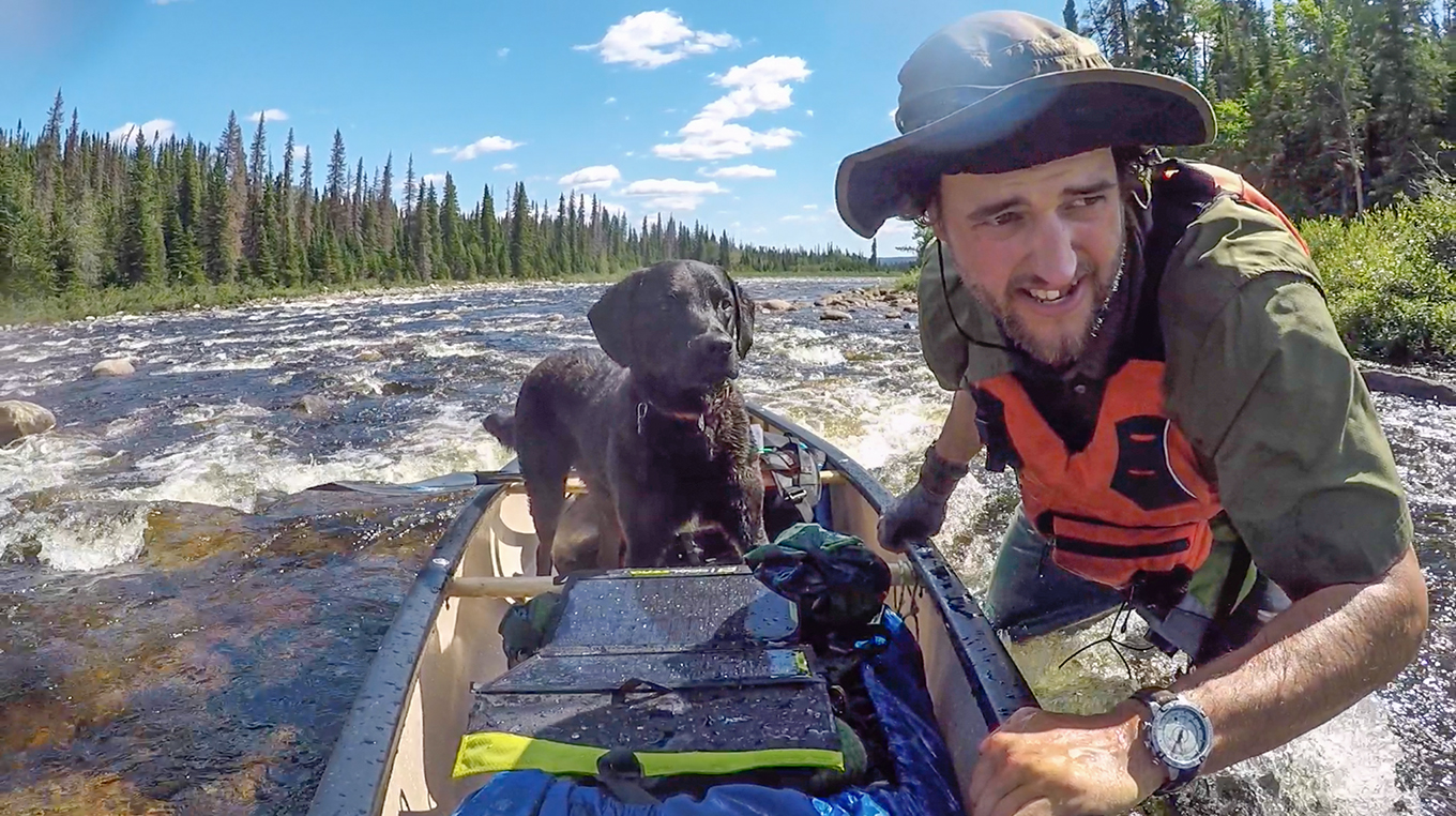 Justin Barbour and his dog, Saku, with canoe in river