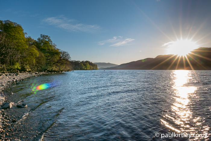 canoe in the distance on Loch Tay with low sun