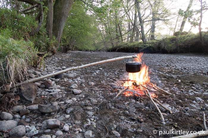 Pot hanger and pot over fire on rocky river bed