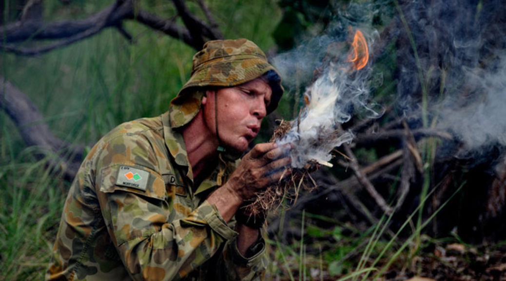 Man in Australian army uniform blowing tinder bundle into flame